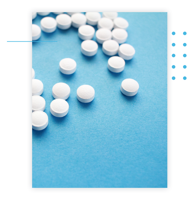 Unlabeled circular medicine tablets scattered on a table.