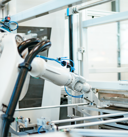 Robotic arm in a lab reaching for a tray of samples.